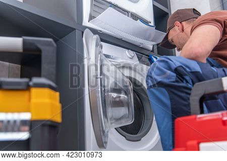Caucasian Technician In His 40s Repairs Broken Washing Machine. Home Appliances Maintenance.