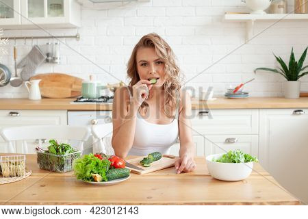 Beautiful Young Woman Is Preparing Vegetable Salad In The Kitchen. Healthy Food. Vegan Salad. Diet A