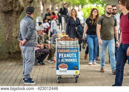 Seller Of Hot Caramelised Peanuts Almonds. London, Britain, May 29, 2021.