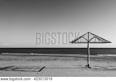 Desolate beach with bare parasol by the sea. Black and white photography, landscape - seascape