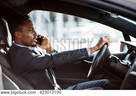 Side View Of African Businessman In Stylish Suit Driving Car And Talking In Mobile. Handsome Busy Ma