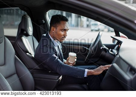 Side View Of Focused African Man Sitting On Drivers Seat With Cup Of Coffee And Using Dashboard For