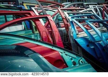 Different Colored Car Doors At A Car Junkyard