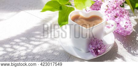 Cappuccino Coffee In A Cup And A Branch Of Lilac On A White Background With Shadows . A Hot Drink. R