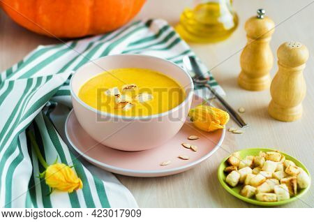 Creamy Pumpkin Soup With Vegetables, Seeds And Croutons In A Bowl On Light Wooden Background. Thanks