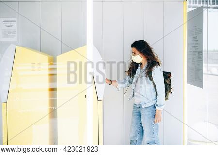 Pretty Young Woman Traveler Wearing Protective Face Mask Withdrawing Money In Cash At Yellow Atm. Mo
