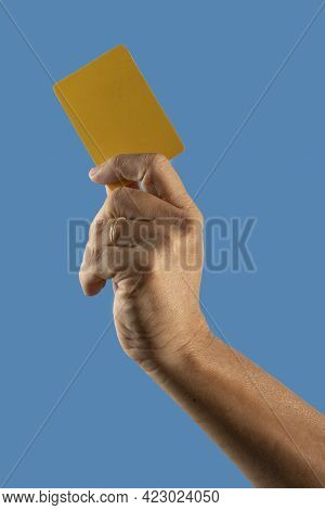 Referee Hand Holding Yellow Punishment Card On Blue Background