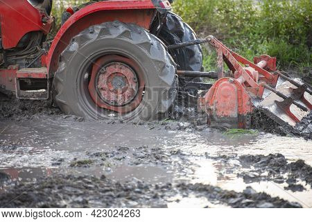 Red Tractor Plowing On Green Rice Field Land, Farmer On Tractor Work Plowing Agriculture In Rainy Se