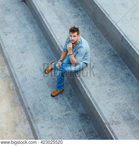 Young man sitting on stairs alone on street high angle view. Social distance in empty city