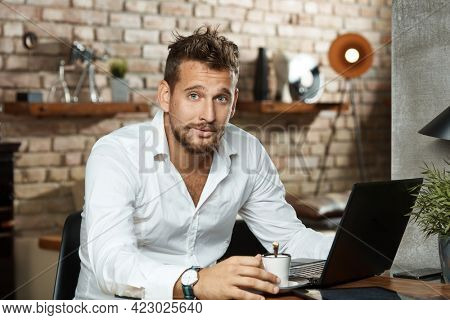 Happy young businessman working from home online. Sitting at desk browsing internet on laptop computer and teleworking in home office.