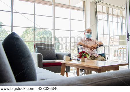 Senior Man At The Nursing Home Concept. A Female Nurse Stands Holding A Wheelchair With An Elderly P