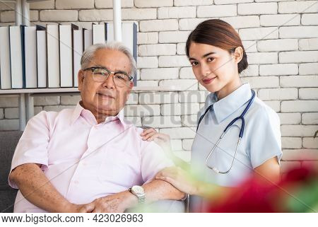 Senior Man At The Nursing Home Concept. Nurse Is With An Elderly Man Sitting On Armchair In Living R