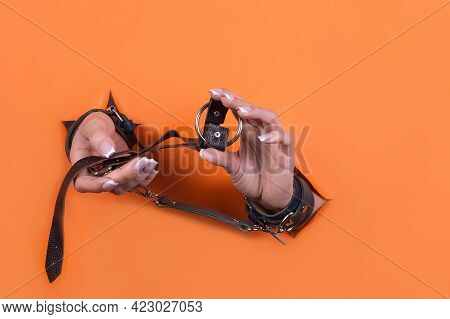 Adult Sex Toys, Minimal Design, Isolated On An Orange Background. Women's Hands In Handcuffs. Bdsm.