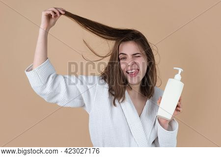 Surprised Amazed Girl Applying Hair Conditioner. Young Woman Applying Hair Mask.