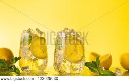 Lemonade with fresh slice lemon and mint leaves. Summer homemade drink. Citrus cold refreshing lemonade.