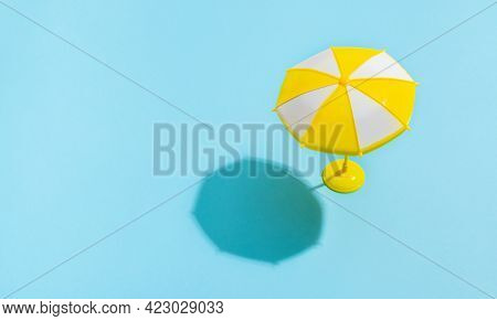 Summer concept. Sun umbrella with sun shadow on blue background. Sun protection concept in summer.