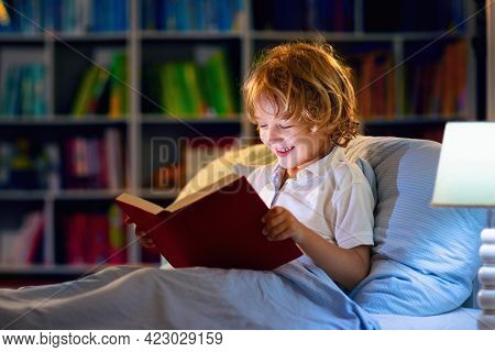 Child Reading Book In Bed. Kids Read At Night. Little Boy With Fairy Tale Books In Bedroom . Educati