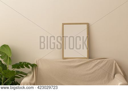 Cozy Couch And Empty Picture Frame On Wall Background