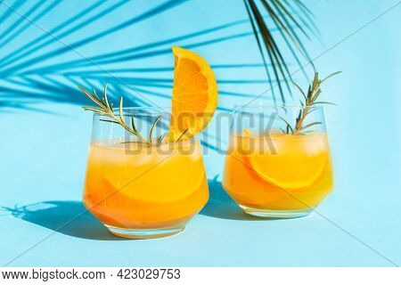 Close-up Lemonade, Orange Cocktail, Refreshing Summer Drink With Ice In A Glass With A Sprig Of Rose