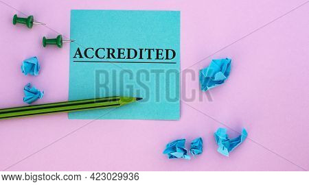 Accredited - Word On A Note Piece Of Paper On A Pink Background With Scattered Blue Crumpled Pieces