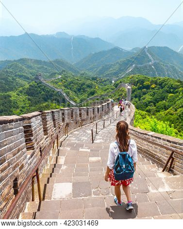 China travel adventure woman tourist backpacker walking backpacking on the Great Wall at famous Badaling destination in Beijing. Asia summer vacation tourism lifestyle. View of mountain landscape.