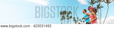 Athlete sport runners couple running landscape banner. Fitness people couple jogging together in summer park outdoor. Horizontal palm trees background. Asian girl, Caucasian friend man.