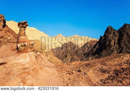 Eilat Mountains. Multicolored landscape formations. Bizarre forms of weathered sandstone in the mountains of Eilat. The rocks are composed of sandstones, igneous and volcanic rocks.
