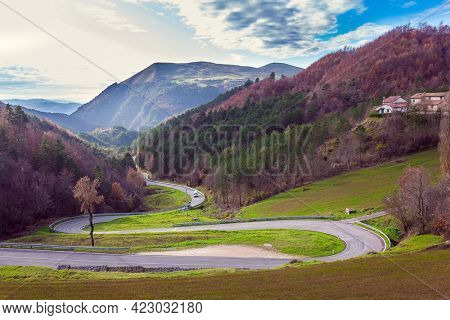 The picturesque mountain slopes are covered with coniferous forest. Winding mountain road