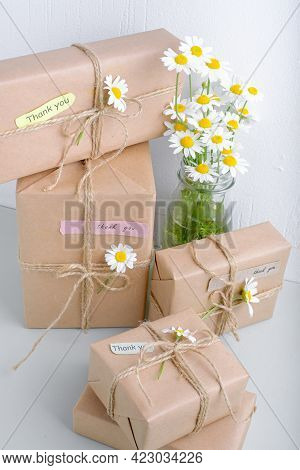 Set Of Gifts Box Wrapped With Brown Craft Paper And Decorated With Natural Chamomile Flowers With Wo