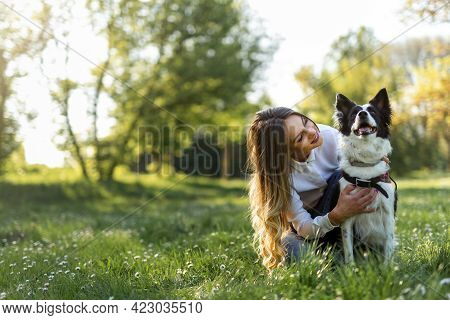 Beautiful Woman With Playful Dog On Fresh Green Meadow