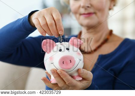 Woman Pensioner Inserting Coin Into Pink Piggy Bank Closeup
