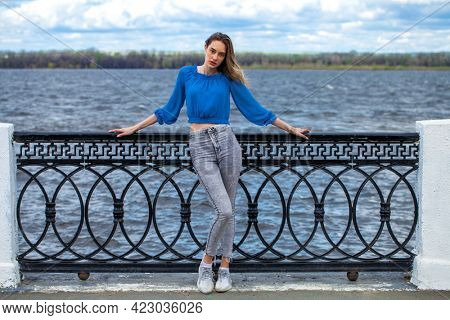 Full length portrait of a young stylish girl in blue blouse and grey jeans