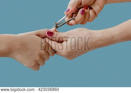 Woman Hand Is Using A Nail Clipper To Cut A Children Fingernails Isolated On Blue Pastel Color Backg