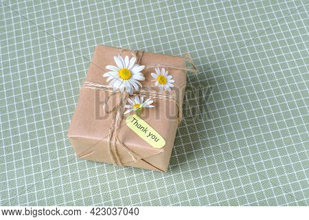 Eco Present Wrapped In Kraft Paper On A Tablecloth In A Cell, On The Table At Home. High Quality Pho