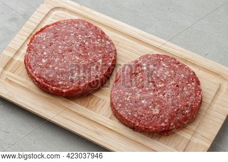 Raw Beef Burger Patty On Wooden Board