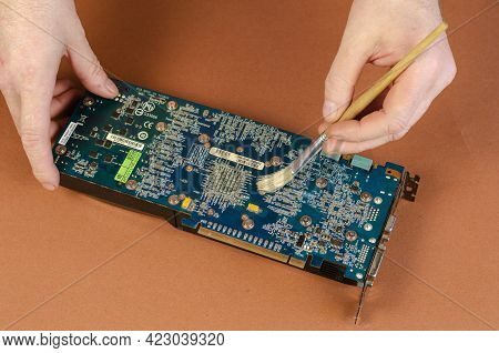 Graphics Card Brand Gigabyte Nvidia Geforce On Brown Background. Man Sweeps Dust Off The Dusty Compu