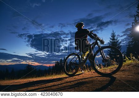 Back View Of Young Man Sitting On Bicycle Under Beautiful Night Sky. Male Bicyclist Resting On Hills