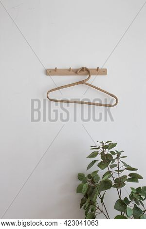 One Wooden Hangers On A White Wall.
