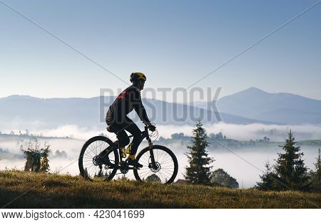 Silhouette Of Man Cyclist In Cycling Suit Riding Bike On Grassy Hill. Male Bicyclist Enjoying The Vi