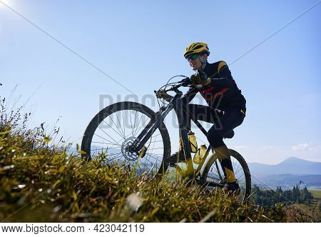 Smiling Man In Safety Helmet And Glasses Cycling Uphill On Sunny Day With Blue Sky On Background. Ma