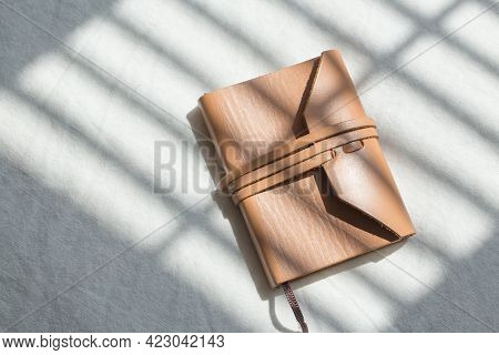 Blank Brown Leather Diary On White Desk.