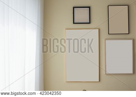 Mockup Of Blank Three Frame Poster On The Wall