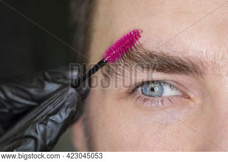 Close Up View For A Portrait Of A Caucasian Male Person Combing His Eyebrow. Macro. Studio Shot. Mid