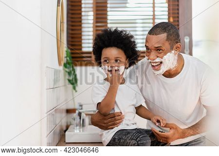 Happy Smiling Black African American Father And Little Son With Shaving Foam On Their Faces Having F