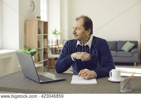 Pensive Smiling Adult Man Sitting At Table With Computer Looking Away