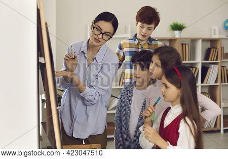 Teacher At Board Explaining Lesson Subject To Student Children Side View Shot