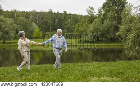 Happy Senior Man And Woman Walking By The River In A Green Park On A Fine Summer Day