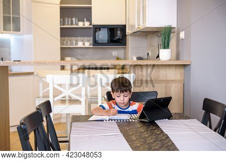 Smart Preteen Schoolboy Doing His Homework With Digital Tablet At Home. Child Using Gadgets On His K