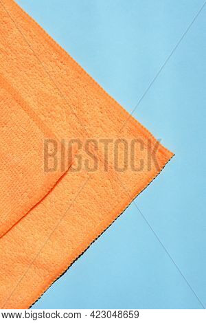 Detail Of An Orange Microfiber Cloth On Blue Paper Background