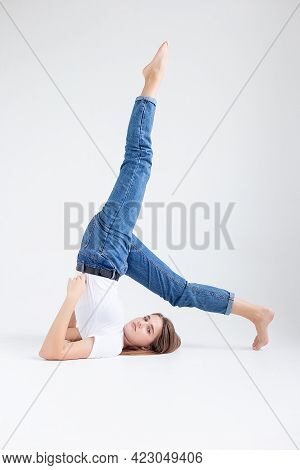 Young Attractive Caucasian Woman With Long Hair In T-shirt And Blue Jeans Isolated On White Backgrou